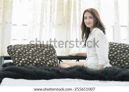 Close up of a happy young woman smile while lying on the bed at home , model is a asian girl - stock photo