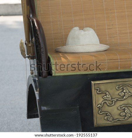 Close-up of a hat on the seat of a rickshaw, Hutong, Xicheng District, Beijing, China - stock photo