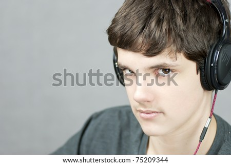 Close-up of a headphone wearing teen looking to camera. - stock photo