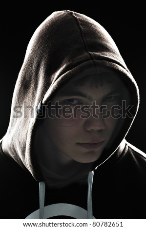 Close up of a hooded teenager looking from the corner of his eyes having a menacing look - stock photo