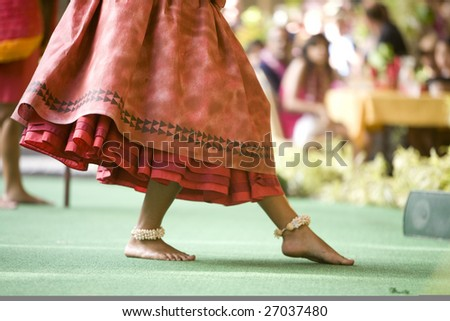 Close up of a hula dancer on a stage, focus on the her feet. - stock photo