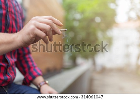 Close up of a human hand holding rolled up joint - stock photo