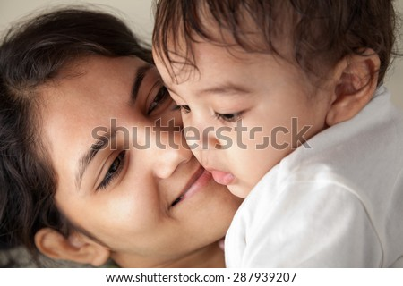Close up of a Indian happy mother looking at her baby with love - stock photo