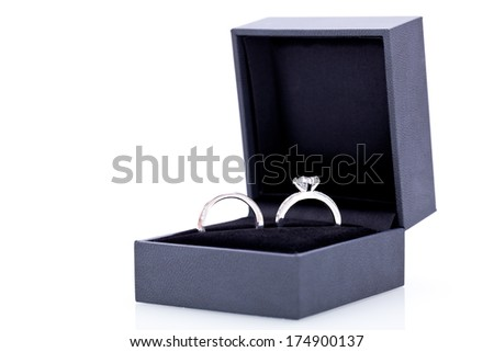 Close-up of a jewelry box with two elegant silver rings from which one with a diamond, symbol of engagement and elegance - stock photo