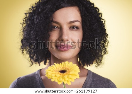 Close up of a joyful woman being happy and holding a flower in her hand, isolated on yellow background. - stock photo