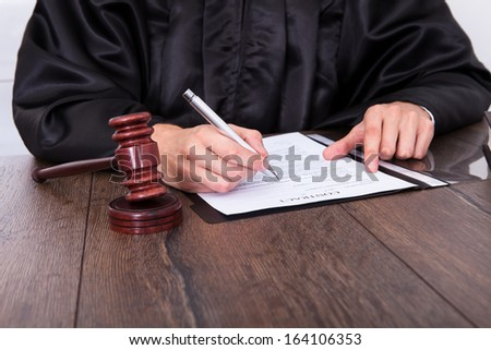 Close-up Of A Judge Hitting Mallet At Desk - stock photo