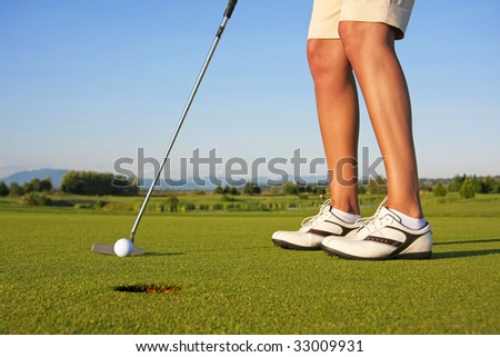 Close up of a lady golfer, putting. - stock photo