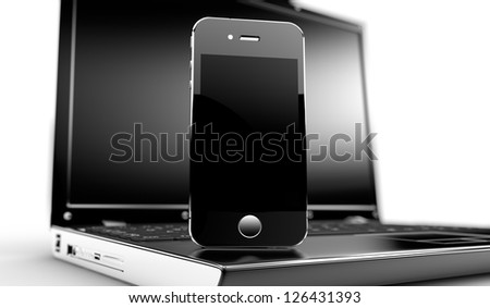 Close up of a laptop with a phone on it - stock photo