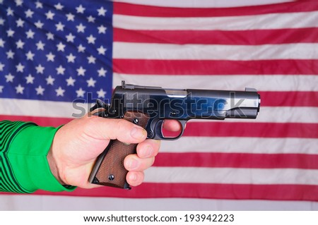 Close-up of a Left-handed shooter holding semi-automatic pistol in front of a US flag - stock photo