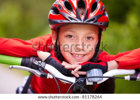 Close-up of a little boy?s face on bike looking at camera and smiling - stock photo