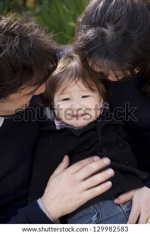 Close up of a little boy surrounded by his parents. Slight blur applied - stock photo