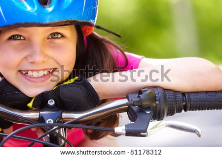 Close-up of a little girl?s face on bike looking at camera and smiling - stock photo