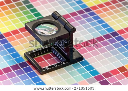 Close-up of a loupe inspecting the very colorful, blurry inkjet test print with color shades in cyan, blue, magenta, red, green, orange, and yellow - stock photo