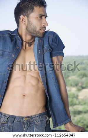 Close-up of a macho man standing in the balcony - stock photo