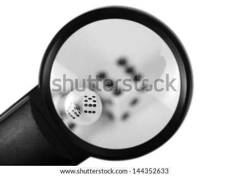 Close-up of a magnifying glass with dices - stock photo