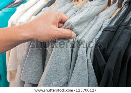 Close-up of a male customer looking for T-shirts in a fashion store - stock photo