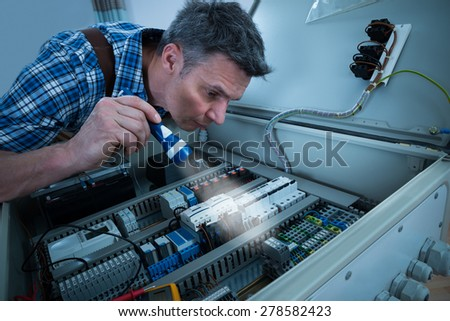 Close-up Of A Male Electrician Analyzing Connection Of Fusebox With Torch - stock photo