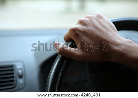 Close-up of a male hand on steering wheel in a modern car in the UK (steering wheel on the right) - stock photo