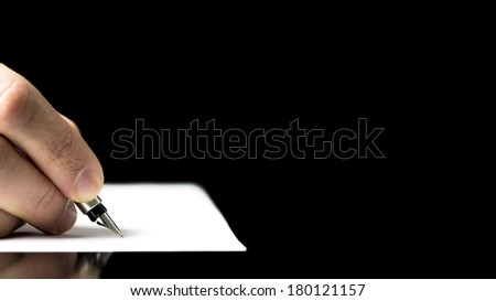 Close-up of a male hand ready to write with an elegant fountain pen on a empty piece of paper, on a glass table, with black copy space. - stock photo