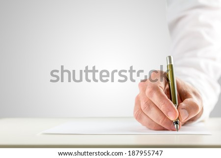 Close-up of a male hand with white sleeve holding a ballpoint in order to start writing on a blank paper placed on the desk, with copy space on gray background. - stock photo