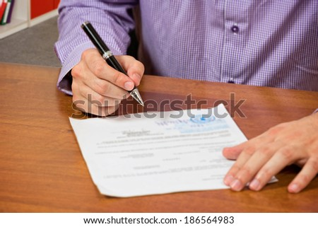 Close up of a male's hand, signing document. - stock photo
