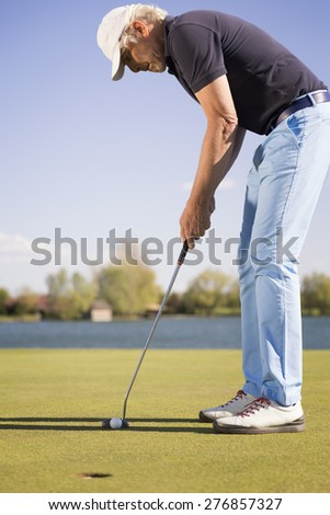 Close up of a male senior golf player putting on green with beautiful lake in background. - stock photo