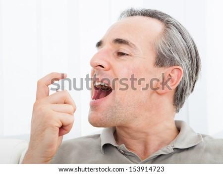 Close-up of a man applying Fresh breath spray - stock photo