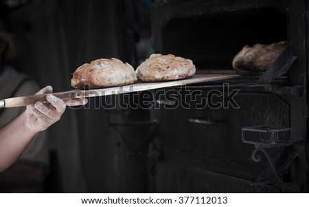 Close-up of a man baker introducing breads in a classic oven - stock photo