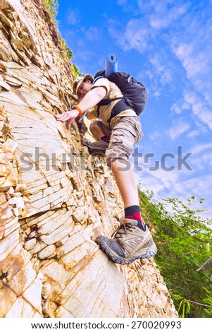 Close up of a man climbing up red rock dressed in hiking shoes, khaki color shorts and t-shirt with black rucksack.   - stock photo