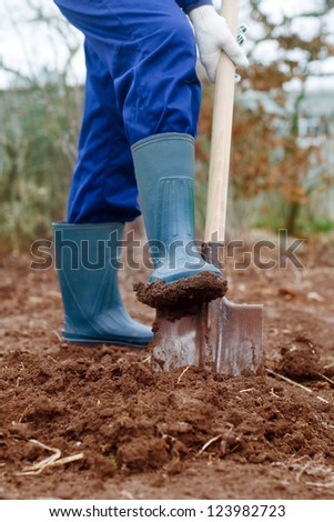 Close up of a man digging soil with shovel in rubber boots and gloves - stock photo