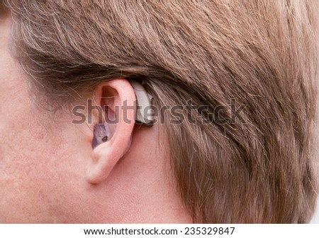 Close-up of a man ear with a high-tech digital hearing aid - stock photo