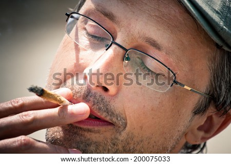 Close up of a man enjoying smoking hashish joint. - stock photo