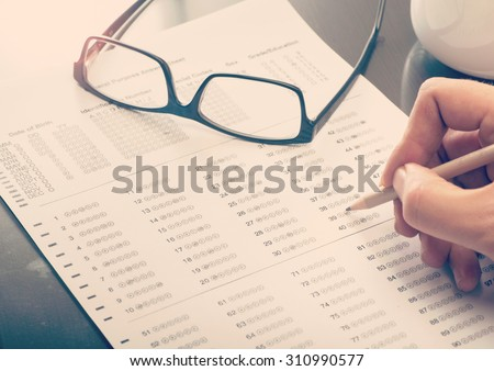 Close up of a man filling a standardized test form - stock photo