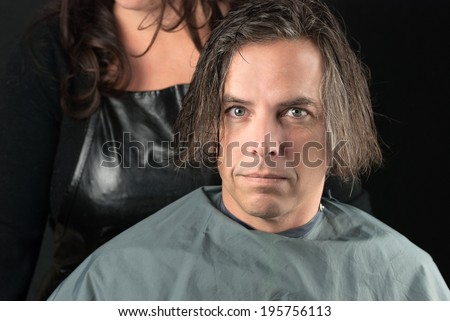 Close-up of a man, his hair newly shampooed, wearing a cape and ready for a hair cut. - stock photo