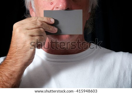Close up of a man holding a grey card over his mouth against a black background wearing white t shirt. Censorship or freedom of speech concept. - stock photo