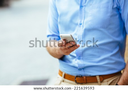 Close-up of a man holding a smartphone in his hand - stock photo