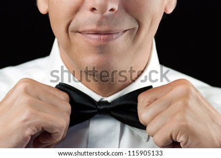 Close-up of a man in a tux straightening his bowtie, two hands, no jacket. - stock photo