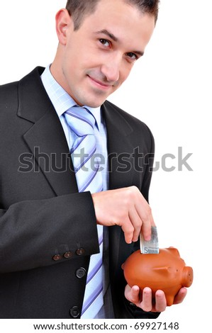 Close up of a man inserting a coin into a piggy bank isolated on white background - stock photo