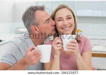 Close-up of a man kissing a happy woman while having coffee in the kitchen at home - stock photo