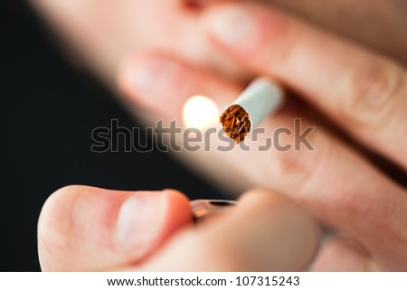 Close up of a man lighting a cigarette against a black background - stock photo