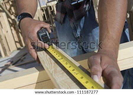 Close-up of a man measuring with measure tape at construction site - stock photo
