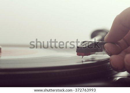 Close up of a man putting a record on turntable - stock photo