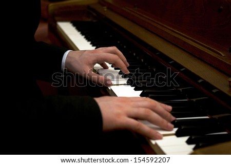 Close up of a man's hands playing a piano - stock photo