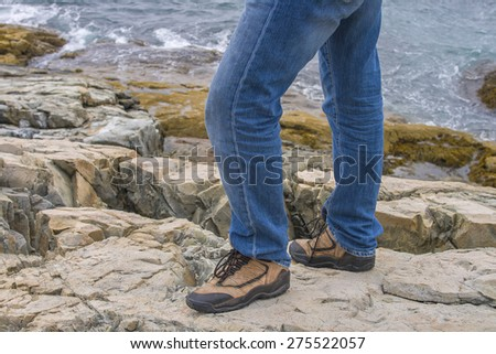Close up of a man's legs in jeans with sturdy shoes on rocks near the sea - stock photo