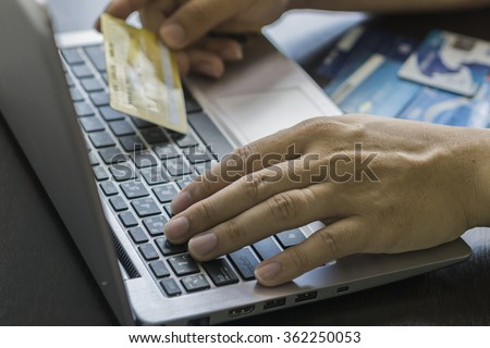 Close Up Of A Man Shopping Online Using Laptop With Credit Card,male hands holding credit card typing numbers on computer keyboard while sitting at home at the wooden table,selective focus  - stock photo