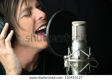 Close-up of a man singing into a condenser microphone. - stock photo