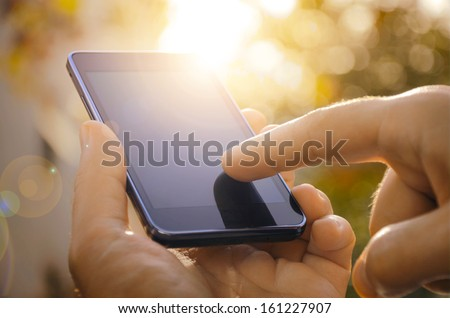 Close up of a man using mobile smart phone outdoor - stock photo