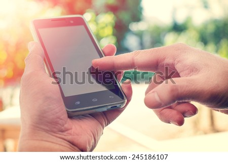 Close up of a man using mobile smart phone outdoor,  nature background. (vintage color tone) - stock photo