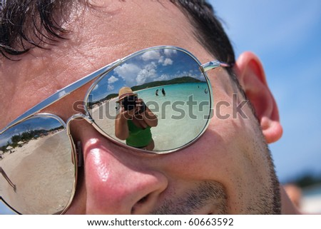 Close up of a man wearing reflective sunglasses in a tropical beach with reflection of the female photographer in the lens. Shallow depth of field. - stock photo