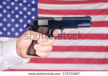 close up of a mans hand holding a 45 ACP 1911 over an American flag - stock photo